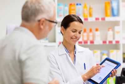 pharmacist and senior customer holding a tablet at pharmacy